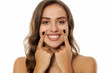 Quadro Portrait of beautiful young woman forced her smile with her fingers on white background