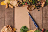 Frame of bright autumn leaves on the boards with a blank page and red apple and blue pen - 176344065