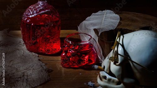 Foto op Aluminium Sap Skull shaped ashtray with glasses and bottles and glasses, skulls , strawberry juice.