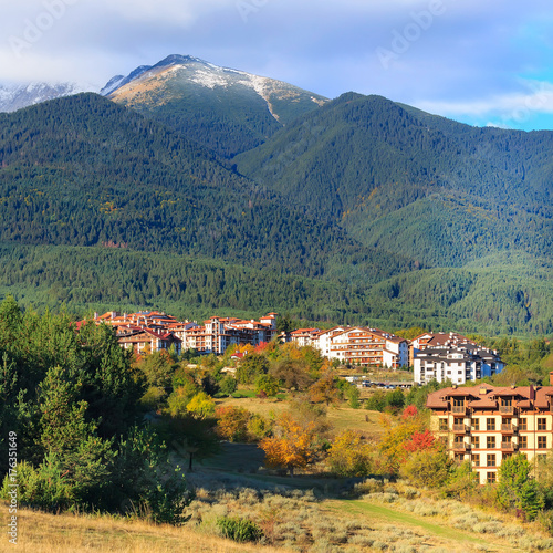 Pirin snow peaks mountains panorama with houses and colorful autumn trees, Bansko, Bulgaria