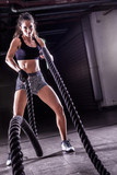 Battle ropes session. Attractive young fit and toned sportswoman working out in fitness  training gym - 176358851