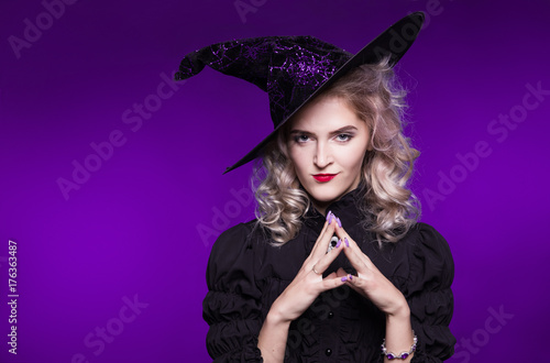 Beautiful, woman, witch, sorceress, blonde, portrait on purple background. American, dress for a costume party Halloween. Bright makeup - 176363487