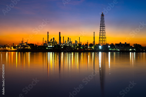 Silhouette oil refinery, tanker ship and petrochemical plant at early morning time beside Chao Phaya river, Thailand Poster