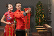 Young Vietnamese couple wearing traditional costumes holding scrolls with New Year couplets in hands while wrapped up in living room decoration