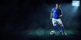 Soccer player performs an action play on a dark background. Player wears unbranded sport uniform. - 176383849