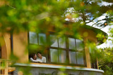 Loving Asian couple in window of their house on early autumn day - 176388064