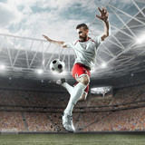 Soccer player performs an action play and beats the ball on a professional stadium. Player wears unbranded sport uniform. - 176389610