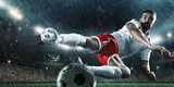 Soccer player performs an action play and beats the ball on a professional rainy stadium. Player wears unbranded sport uniform. - 176390218