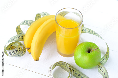 In de dag Sap healthy eating, dieting, slimming and weigh loss concept - close up of green apple, banana, orange, juice, measuring tape.