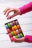Hand takes macaroon from box of sweet on the table - 176409066