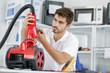 handsome young repairman fixing vacuum cleaner