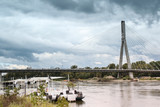 Landscape with dramatic sky over a restaurant on the barge and the bridge across the Vistula River in Warsaw - 176413074