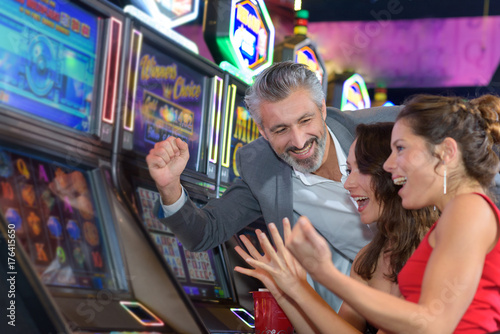 people gambling in a casino playing slot machine Poster