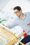 talented mature painter is working with inspiration - 176422483