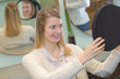 Lady looking in reflected mirror to see hairstyle