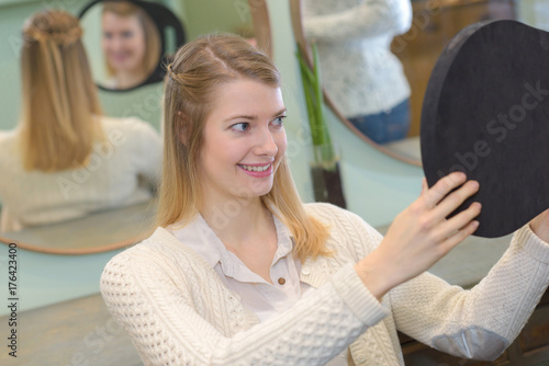 Aluminium Kapsalon Lady looking in reflected mirror to see hairstyle