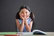 Composite image of portrait of girl doing homework at desk