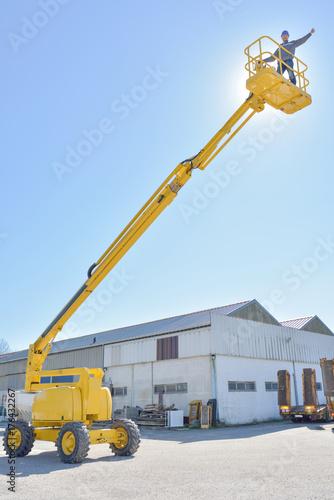 worker on construction crane yellow