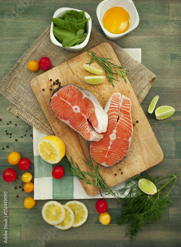 Two fresh raw salmon steaks with lemon, tomatoes on the rustic table - 176449090