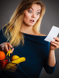 Shocked woman holding shopping basket with fruits