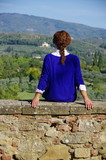 Young woman in blue shirt sitting on a stone wall looking at the Tuscany countryside - 176455655