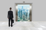 Businessman With Briefcase Looking At Modern Elevator - 176465475
