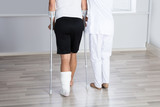Physiotherapist Helping Injured Man To Walk With Crutches - 176466877