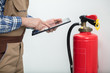 Quadro Technician Using Digital Tablet To Check Fire Extinguisher