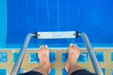 Foot going to down the staircase of the pool. - 176474063