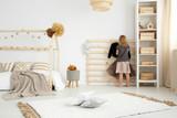 Girl in scandinavian style bedroom - 176480431