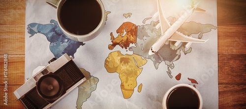 Overhead view of coffee cups with toy airplane and camera on map