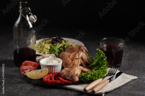 Fried chicken wings and plate with pasta on a dark background - 176485823