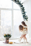 Christmas and new year 2018. Little sisters are waiting for Santa Claus at the window on Christmas Eve