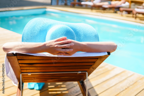 Relaxing woman near luxury swimming pool. Poster