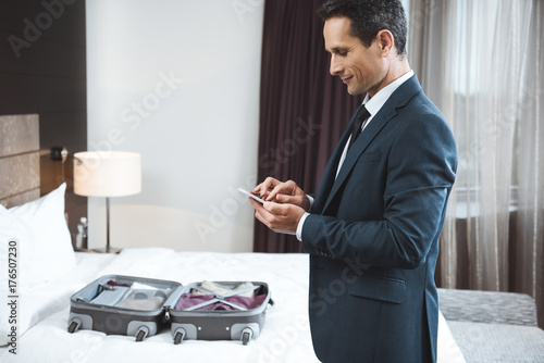 Businessman using phone in hotel room