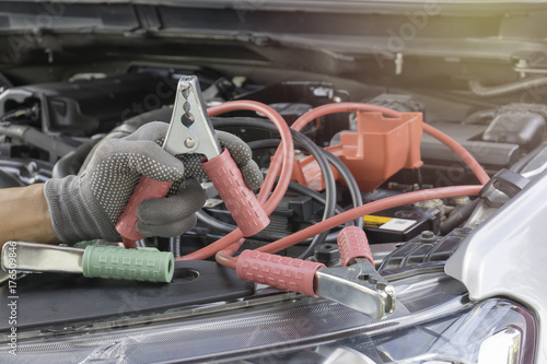 Car mechanic uses battery jumper cables charge a dead battery. Poster