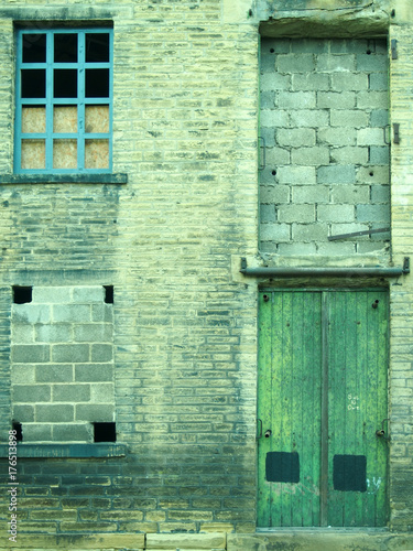 Foto op Plexiglas Oude verlaten gebouwen neglected and abandoned industrial warehouse and factory building with bricked up windows and green door in halifax yorkshire in britain