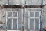 Two windows on the facade of the old house closed mesh for repair - 176521261