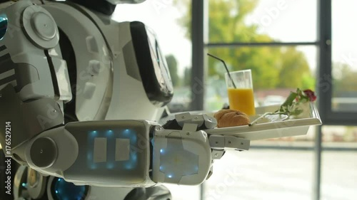 Careful robot carrying tray with breakfast