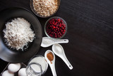 Flour, oatmeal, berries, milk and eggs, standing on a black wooden table - 176538009