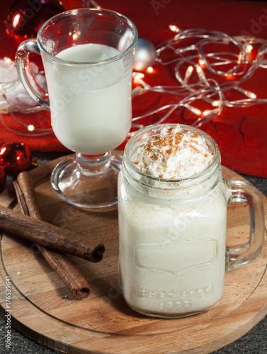 Aluminium Milkshake Christmas eggnog in the glass of mulled wine with cream and cinnamon and Christmas garland