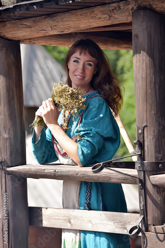 Viking woman, brunette in a blue linen dress, on the walls of the wooden old house Poster