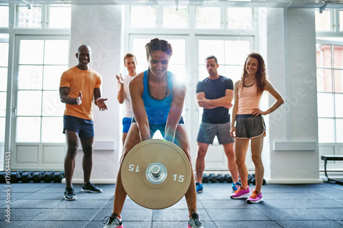 Fit woman lifting weights with friends watching in the backgroun