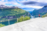 Tourist looking at Geirangerfjord from Flydasjuvet viewpoint Norway - 176560237