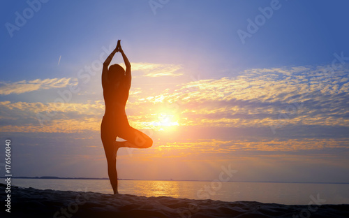 Female silhouette doing yoga asana at sunrise with hands raised to sun