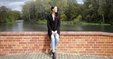 Beautiful woman in black jacket sitting on bridge and enjoying weather during walk in autumn park on sunny day. - 176564605
