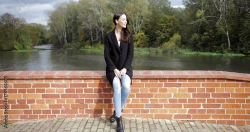 Fototapeta Beautiful woman in black jacket sitting on bridge and enjoying weather during walk in autumn park on sunny day.