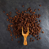 Coffee beans in a wooden scoop on slate plate background - 176566681
