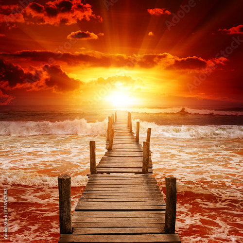 Poster Rood traf. Wooden pier for boats in ocean.