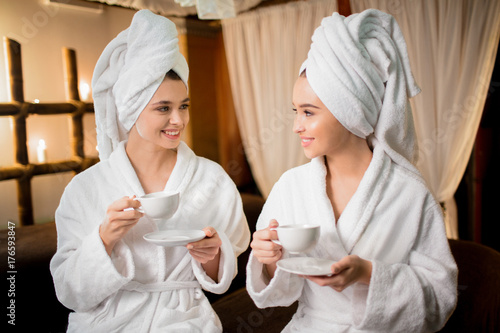 Fotobehang Spa Friendly girls in bathrobes and towels on heads talking by cup of toning herbal tea after spa massage in beauty salon
